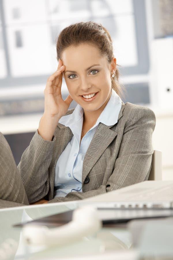 Attraktives Mädchen, das einen Bruch beim Bürolächeln nimmt lizenzfreie stockbilder
