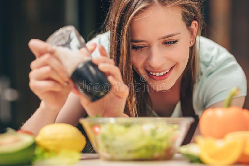 Attraktives Mädchen, das Salat zubereitet lizenzfreie stockfotografie
