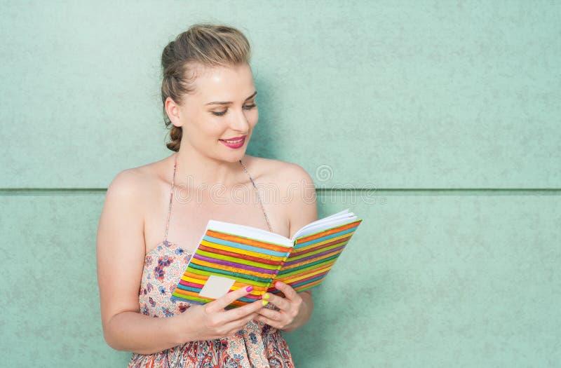 Attraktives Mädchen, das Tagebuch oder Tagesordnung und Ablesen hält stockbilder