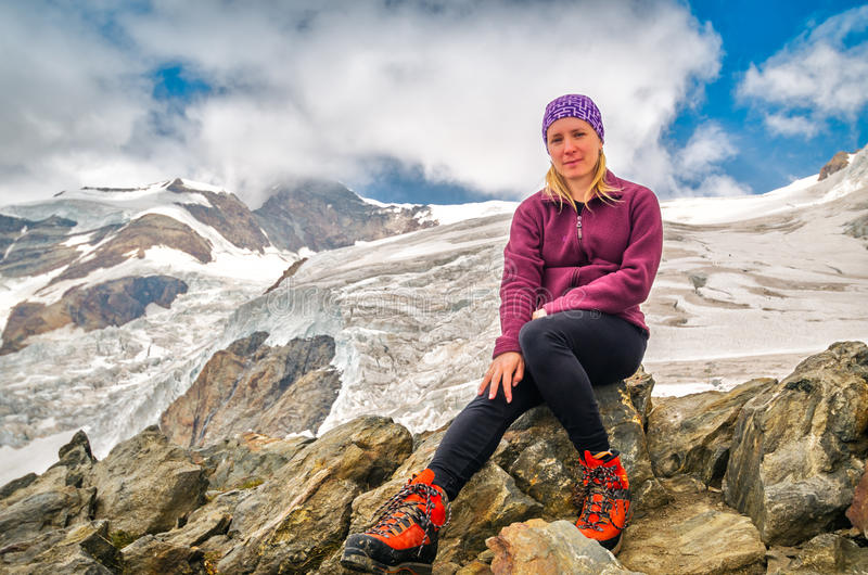 Attraktives Mädchen, das vor dem Gletscher in den Alpen sitzt stockfoto