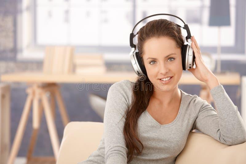 Attraktives Mädchen, das zu Hause lächelnde Musik hört stockbild