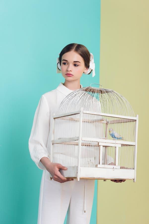 attraktives Mädchen in der modischen weißen Ausstattung mit Papageien im Käfig auf Türkis lizenzfreie stockfotos