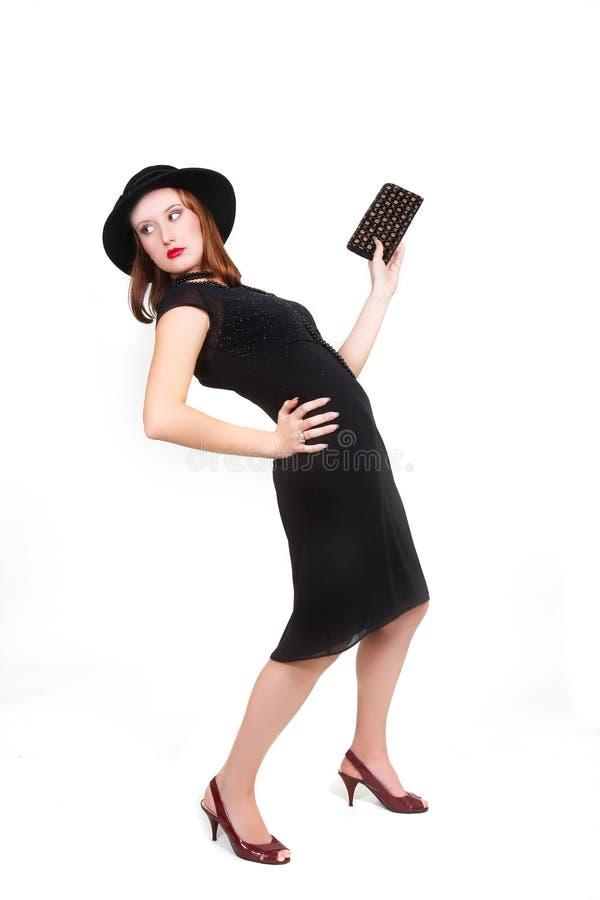 Attraktives Mädchen in der schwarzen Kleid- und Hutaufstellung stockbilder