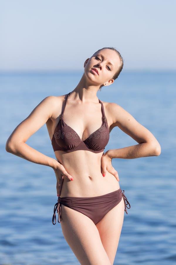 Attraktives Mädchen im Bikini, der die Arme in die Seite gestemmt in dem Meer aufwirft stockfoto