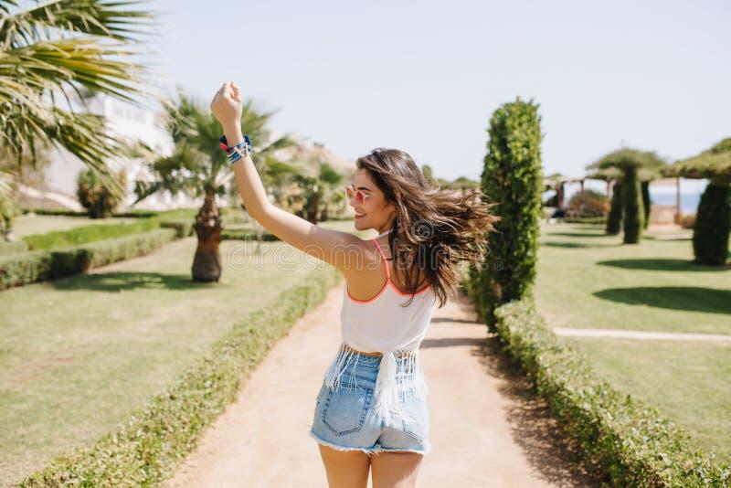 Attraktives Mädchen im lustigen Tanzen des in guter Verfassung mit dem Haar, das, Sommerferien im exotischen Land genießend welle stockfotografie