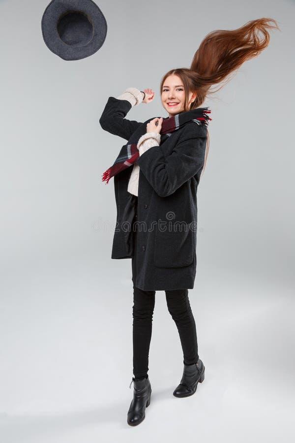 Attraktives Mädchen im Studio auf lächelndem geworfenem Hut des schwarzen Hintergrundes in der Luft stockfotos