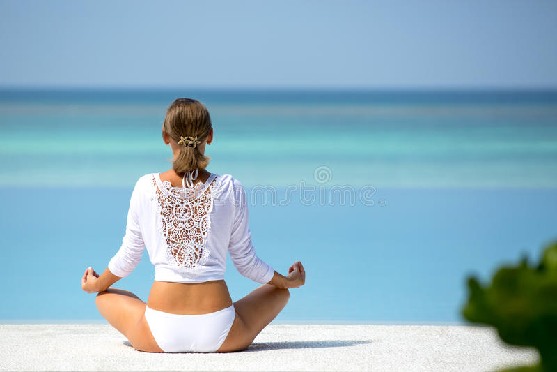 Attraktives Mädchen im weißen übenden Yoga auf dem tropischen Strand auf der Ozeanküste Malediven stockfotografie