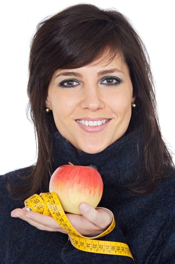 Attraktives Mädchen mit Apfel- und Bandmaß in der Hand stockfotos