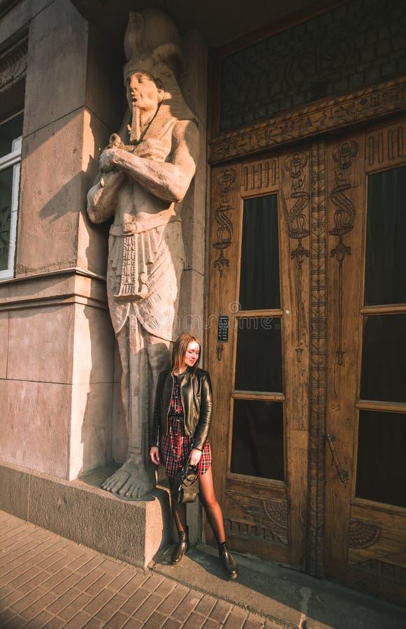 Attraktives Mädchen mit dem blonden Haar in einem Kleid in einem Käfig und in einer schwarzen Lederjacke belichtet durch die Sonn lizenzfreie stockbilder