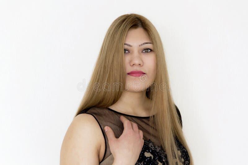 Attraktives Mädchen mit dem braunen geraden Haar, wenn schwarzes Kleid geglättet wird stockbilder