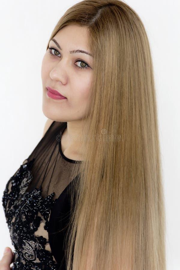Attraktives Mädchen mit dem braunen geraden Haar, wenn schwarzes Kleid geglättet wird stockfotografie