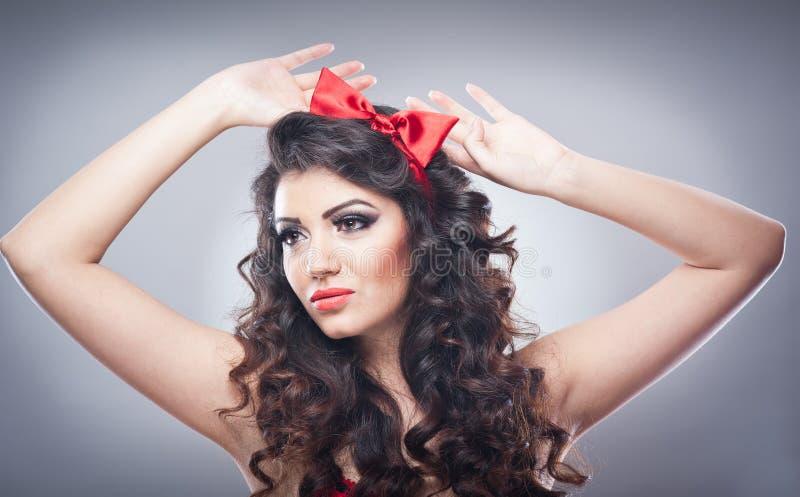 Attraktives Mädchen mit einem roten Bogen auf ihrem Haupt- und roten BH senden einen Kuss Pinupmodell auf grauem Hintergrund Schö stockbild