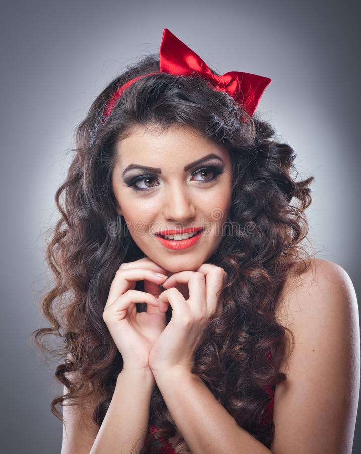 Attraktives Mädchen mit einem roten Bogen auf ihrem Haupt- und roten BH senden einen Kuss Pinupmodell auf grauem Hintergrund Schö stockbilder