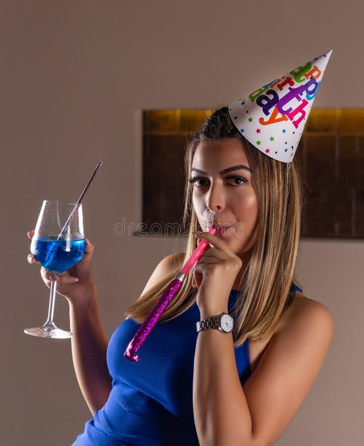 Attraktives Mädchen mit musikalischem Ausblasen und blauer Lagune des Cocktails in der Hand und Kappe auf dem Kopf feiert ihren G lizenzfreie stockfotos