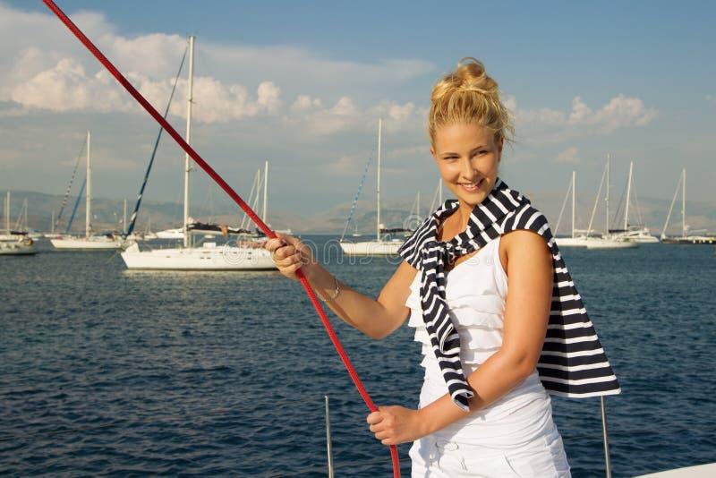 Attraktives Mädchensegeln auf einer Yacht am Sommertag stockfotos