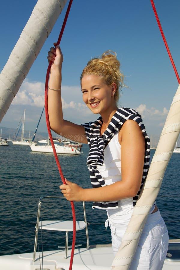 Attraktives Mädchensegeln auf einer Yacht am Sommertag lizenzfreies stockfoto