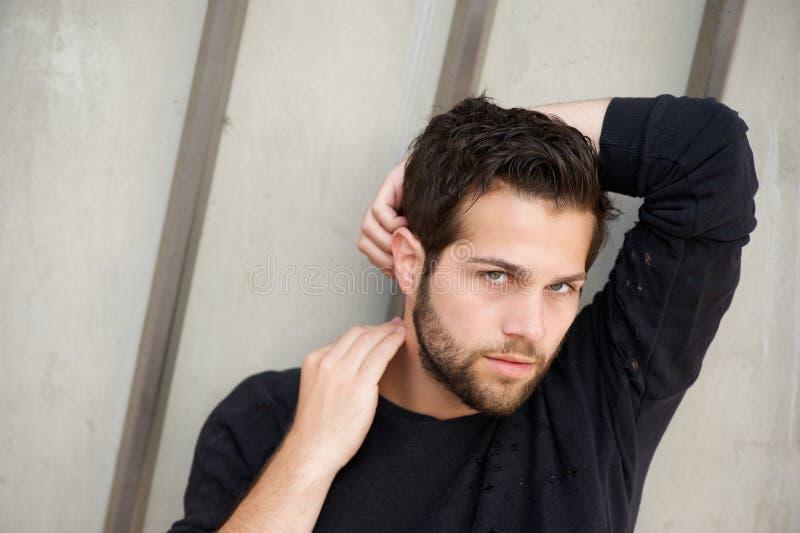 Attraktives männliches Mode-Modell, das mit den Händen hinter Kopf aufwirft stockfotografie