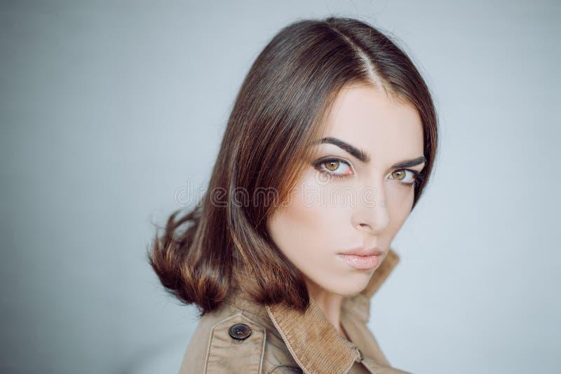 Attraktives M?dchen mit perfekter Haut Make-up, glatte Haut Sch?nheitsfrau im Studio auf grauem Hintergrund Gl?ckliches junges M? lizenzfreie stockfotografie