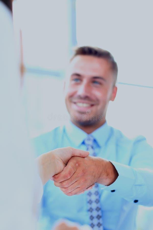 Attraktives Mann- und Frauengeschäft team, Hände am Bürogebäude rüttelnd lizenzfreies stockbild