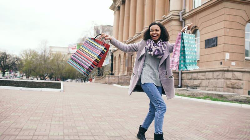 Attraktives Mischrassemädchentanzen und haben Spaß beim Gehen hinunter die Straße mit Taschen Glückliche junge Frau, die nachher  stockfotos