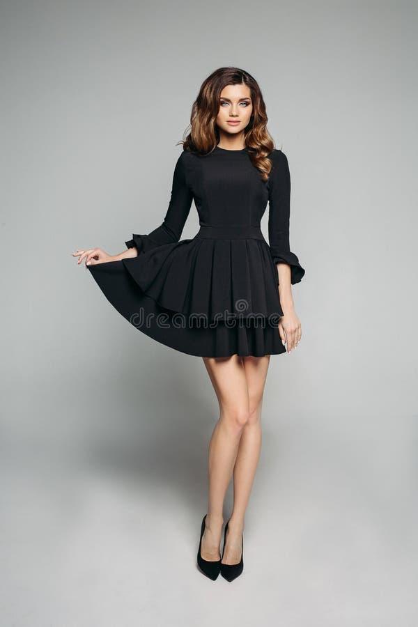 Attraktives Modell mit dem gewellten Haar des Brunette im klassischen fantastischen schwarzen Kleid und in den Fersen lizenzfreie stockfotografie