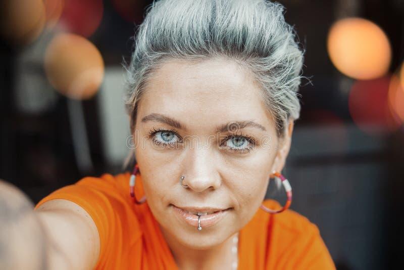 Attraktives nachdenkliches blondes Mädchen im orange T-Shirt, das selfie am Café macht lizenzfreie stockbilder