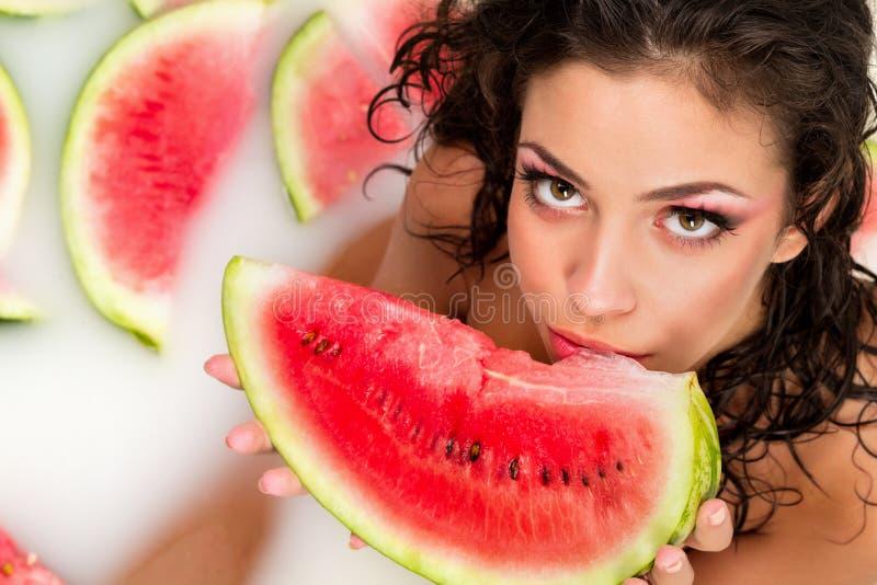 Mädchen genießt ein Bad mit Milch und Wassermelone. lizenzfreie stockfotos