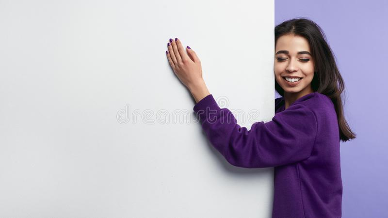 Attraktives nettes Mädchen, das eine weiße vertikale Fahne des freien Raumes mit geschlossenen Augen und toothy dem Lächeln, loka stockfotografie