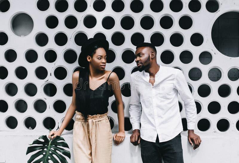Attraktives Paar, beim Zusammenbringen kleidet das Lächeln an der Kamera auf Weiß lizenzfreies stockfoto