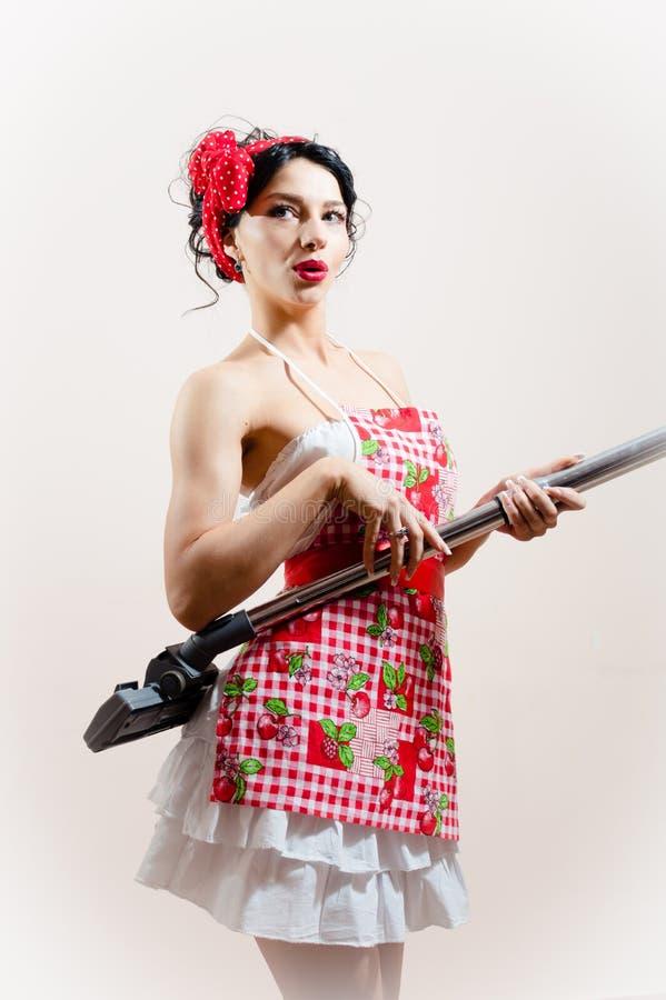 Attraktives Pin-up-Girl der schönen lustigen Hausfraufrau, das Staubsauger als Gitarre auf Weiß spielt lizenzfreies stockbild