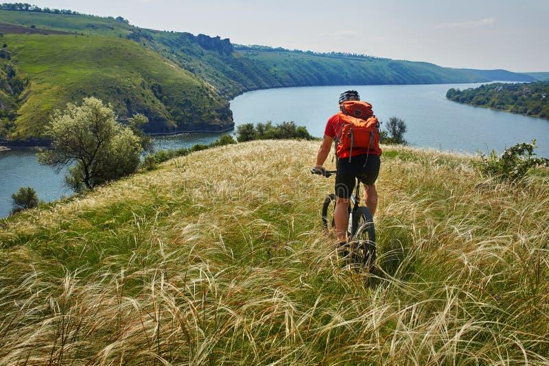 Attraktives Radfahrerreiten-mountainbike auf der Wiese über Fluss in der Sommersaison in der Landschaft stockbild