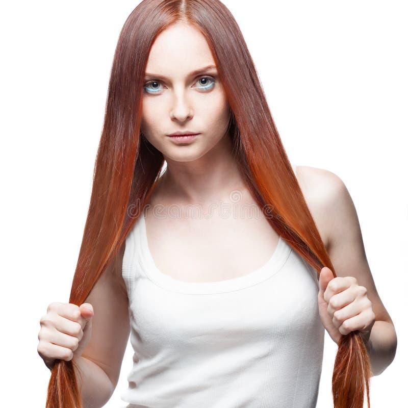 Attraktives rotes Mädchen, das ihr Haar hält lizenzfreie stockfotografie
