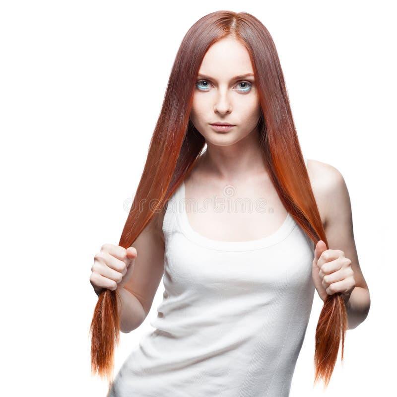 Attraktives rotes Mädchen, das ihr Haar hält lizenzfreies stockfoto