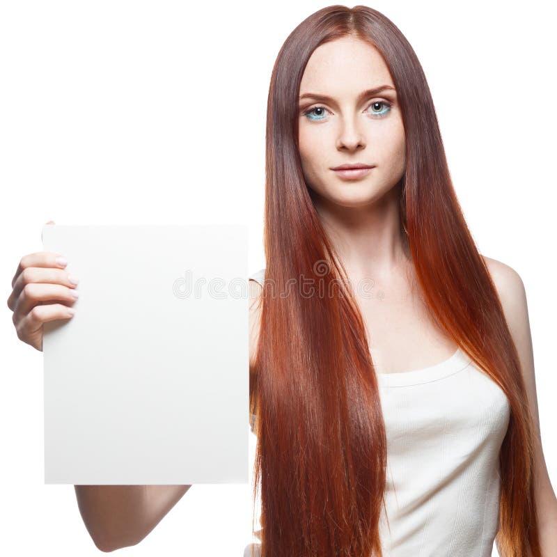 Attraktives rotes Mädchen, das Zeichen hält lizenzfreies stockfoto