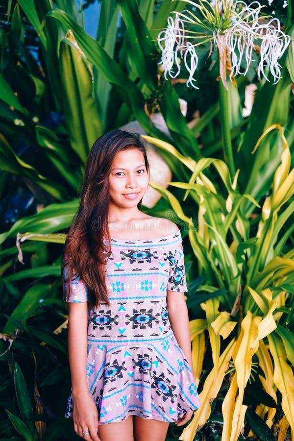 Attraktives schönes asiatisches Mädchenporträt mit dem langen aufwerfenden Haar, auf dem Grünpflanzehintergrund stockfotos