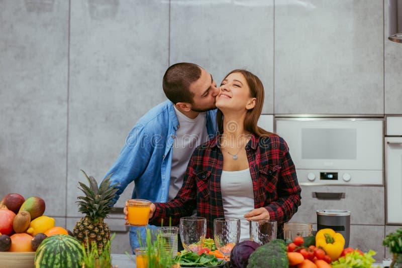 Attraktives Schauen der romantischen jungen Paare, zusammen zusammen machend das gesunde Frühstück von den Obst und Gemüse von stockfoto