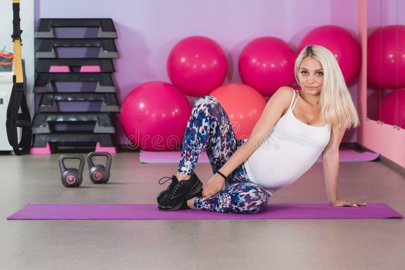 Attraktives schwangere Frau ` s, das Yoga in der Turnhalle mit dem Schritt aerob, gesunder Lebensstil tut stockfoto
