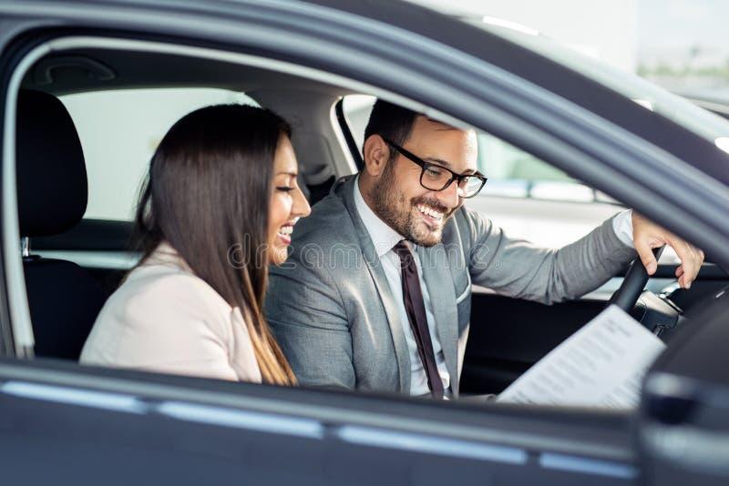 Attraktives Verkäuferinvertretungsinnere eines Autos zum Kunden lizenzfreie stockfotos