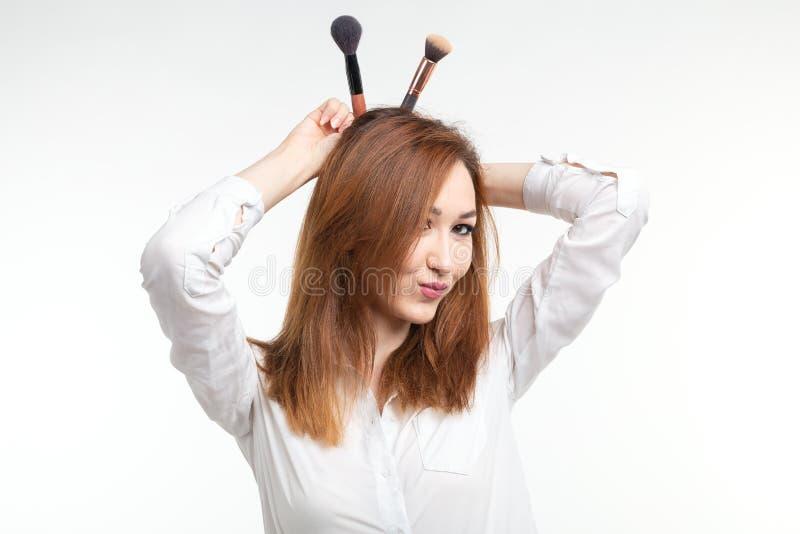 Attraktives visagist oder koreanischer Make-upkünstler, die herum mit Make-upbürsten auf weißem Hintergrund täuschen stockfotografie