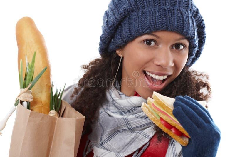 Attraktives weibliches beißendes Sandwich an der Winterzeit lizenzfreie stockfotografie