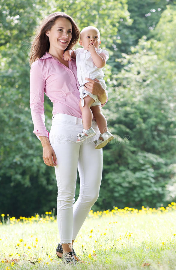Attraktives weibliches lächelndes und haltenes Baby im Park lizenzfreie stockfotos