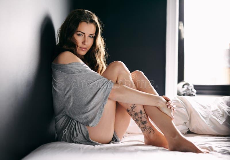 Attraktives weibliches Modell auf Bett stockfotografie