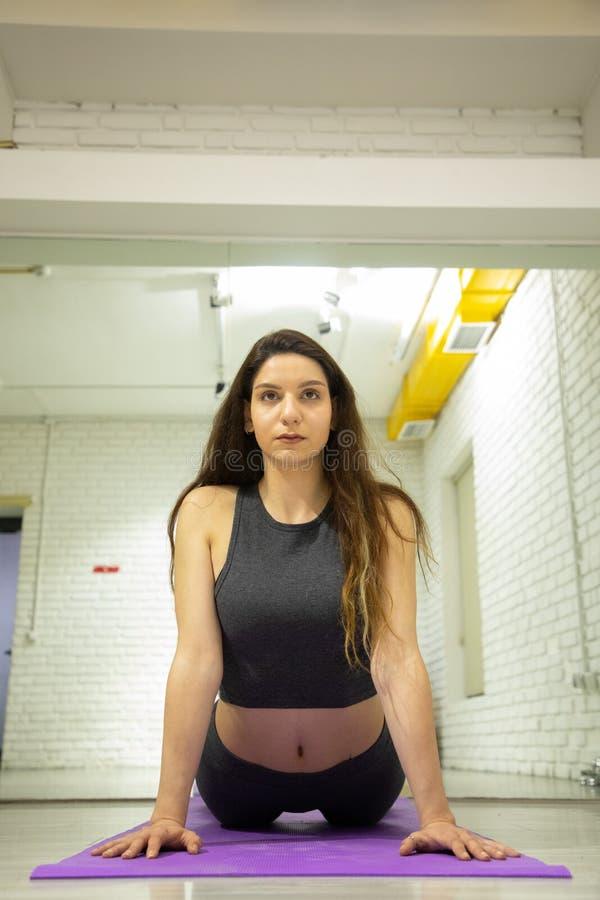 Attraktives weibliches Modell in der Yogaausstattung, die Yoga tut stockfoto