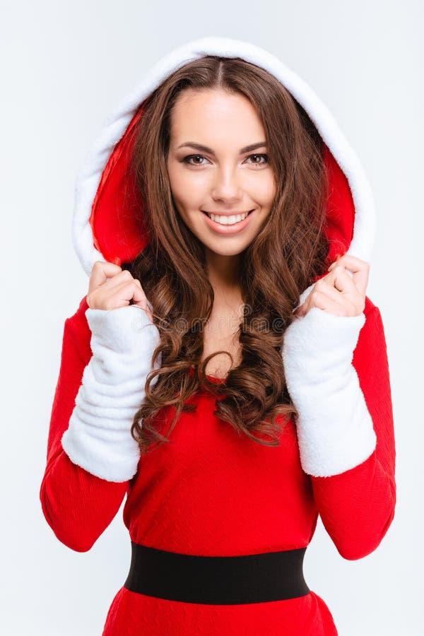 Attraktives zufriedenes Mädchen in rotem Weihnachtsmann-Kostüm mit Haube stockfoto