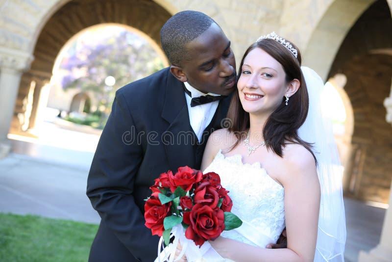 Attraktives zwischen verschiedenen Rassen Hochzeits-Paar-Küssen lizenzfreie stockfotos