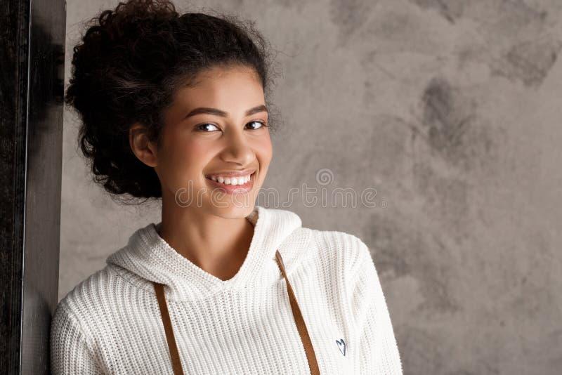Attraktivt afrikanskt le för flicka som poserar över beige bakgrund arkivfoton
