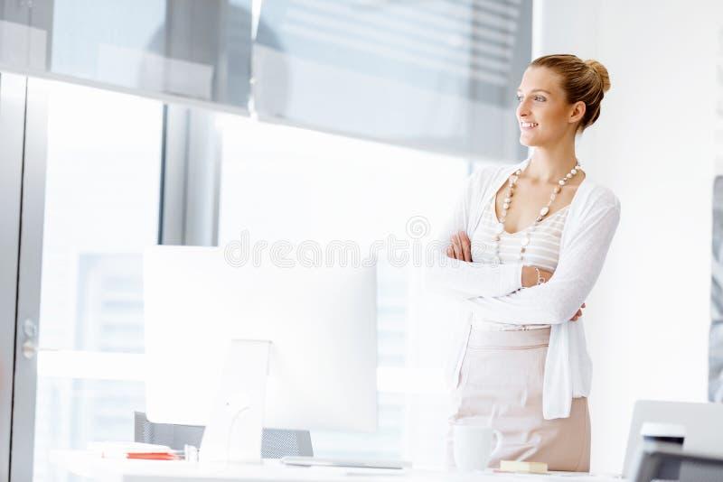 Attraktivt anseende för kontorsarbetare bredvid fönster royaltyfria foton