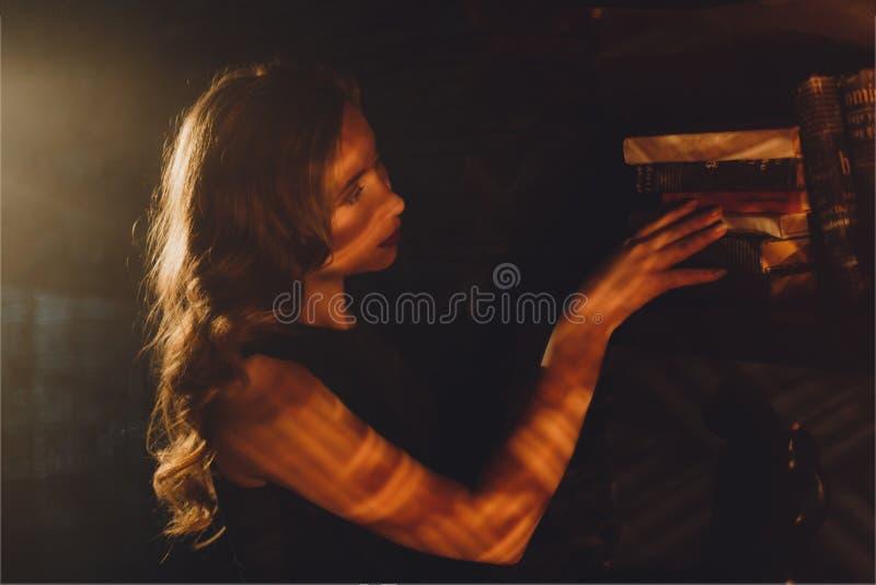 Attraktivt anseende för ung kvinna i stråle av ljus och att trycka på en bok royaltyfri foto
