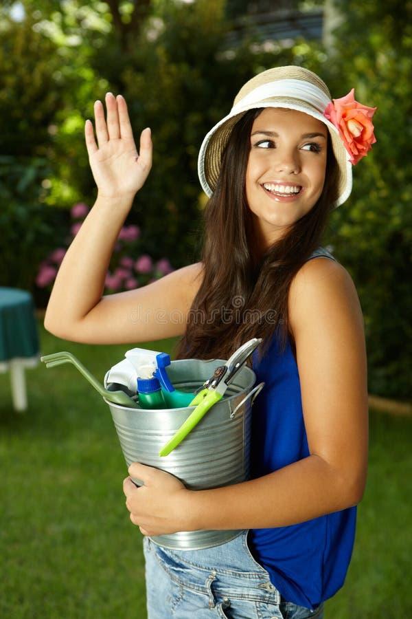 Attraktivt arbeta i trädgården vinka för flicka royaltyfria foton