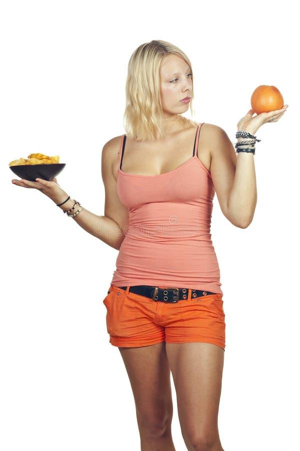 attraktivt avgöra äter skräp för matfruktflickan till royaltyfria bilder